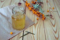 Miel dans un pot en verre et une branche de mer-nerprun Photo libre de droits