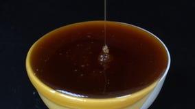 Miel de colada en el cuenco blanco Goteo de la miel del primer en el fondo negro, macro almacen de video