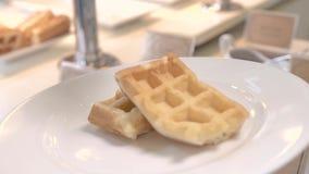 Miel de colada en las galletas belgas en la placa blanca Galletas cocidas dulces con el jarabe de arce para el desayuno tradicion almacen de video