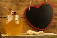 Miel de cristal del tarro con el drizzler, canela en fondo de madera Fotografía de archivo