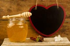 Miel de cristal del tarro con el drizzler, canela, flores en fondo de madera Imagen de archivo libre de regalías