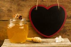 Miel de cristal del tarro con el drizzler, canela, flores en fondo de madera Imágenes de archivo libres de regalías