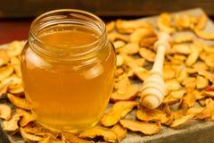 Miel de cristal del tarro con el drizzler, con las manzanas secadas en fondo de madera Fotografía de archivo libre de regalías
