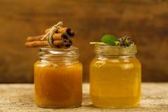 Miel de dos pequeña tarros con canela y flores en fondo de madera Fotos de archivo