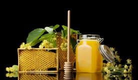 Miel de la abeja en tarro con la tapa, el panal y el agitador de madera aislados en negro Imágenes de archivo libres de regalías