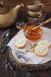 Miel de la lavanda en el tarro de cristal, la lavanda floreciente y rebanadas de baguette Foto de archivo