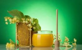 Miel de mayo en tarro, agitador de madera y marco con el panal, en verde Imagen de archivo