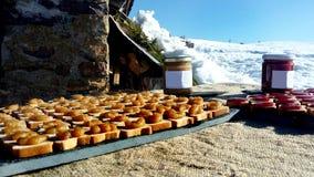 Miel de montagne et confiture sur un plateau d'ardoise hors d'une hutte de montagne un jour ensoleillé - main obtenant pour la dé images stock