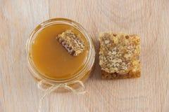Miel de oro en el peine en un tarro y un limón amarillo Imagenes de archivo
