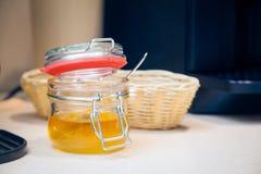 Miel de oro en un tarro de cristal Fotografía de archivo
