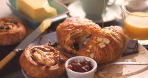 Miel de versement au-dessus d'un petit déjeuner français avec les pâtisseries et le jus d'orange Images stock