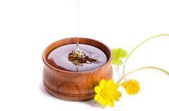 Miel de versement dans la cuvette en bois avec les fleurs jaunes Image stock