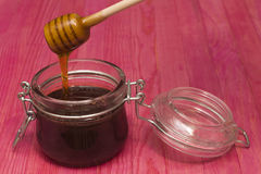 Miel de versement dans le pot en verre sur la table rose Photographie stock