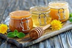 Miel del alforfón, del tilo y de la flor en los tarros de cristal Foto de archivo libre de regalías
