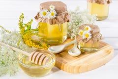 Miel del líquido de la luz natural Miel en los tarros de cristal y cazo con las flores salvajes Foto de archivo
