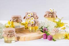 Miel del líquido de la luz natural Miel en los tarros de cristal y cazo con las flores salvajes Fotos de archivo libres de regalías