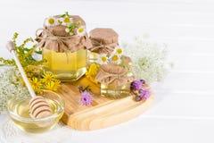 Miel del líquido de la luz natural Miel en los tarros de cristal y cazo con las flores salvajes Imagenes de archivo