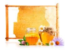 Miel dulce en el tarro de cristal con la cuchara y las flores Fotos de archivo