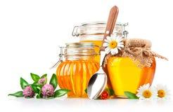 Miel dulce en el tarro de cristal con la cuchara y las flores Imágenes de archivo libres de regalías