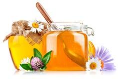 Miel dulce en el tarro de cristal con la cuchara y las flores Fotografía de archivo