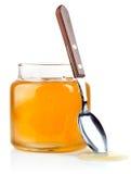 Miel dulce en el tarro de cristal con la cuchara y las flores Fotos de archivo libres de regalías