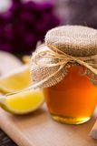 Miel dulce en el tarro y el limón de cristal Fotografía de archivo
