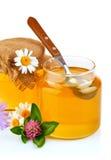 Miel dulce en los tarros de cristal con la cuchara y las flores Fotos de archivo
