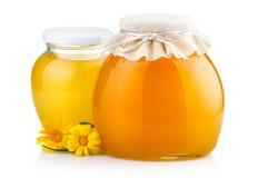 Miel dulce en los tarros de cristal con las flores aisladas en blanco Fotos de archivo