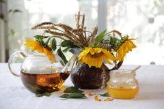 Miel en el banco transparente, el té y un ramo de girasoles Imagen de archivo libre de regalías