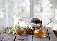 Miel en el banco transparente, la leche en un jarro y el té en un transparen Imagen de archivo