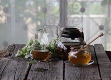 Miel en el banco transparente, la leche en un jarro y el té en un transparen Fotografía de archivo