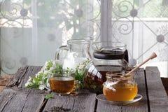 Miel en el banco transparente, la leche en un jarro y el té en un transparen Foto de archivo libre de regalías