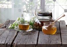Miel en el banco transparente, la leche en un jarro y el té en un transparen Fotos de archivo libres de regalías