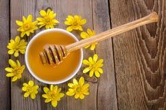 Miel en el bol de vidrio, el cazo y las flores amarillas alrededor de él Fotografía de archivo