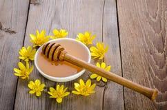 Miel en el bol de vidrio, el cazo y las flores amarillas alrededor de él Foto de archivo libre de regalías