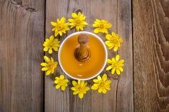 Miel en el bol de vidrio, el cazo y las flores amarillas alrededor de él Fotos de archivo