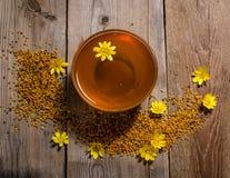 Miel en el bol de vidrio, el polen y las flores amarillas alrededor de él Imagen de archivo libre de regalías