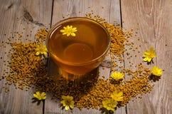 Miel en el bol de vidrio, el polen y las flores amarillas alrededor de él Fotografía de archivo libre de regalías