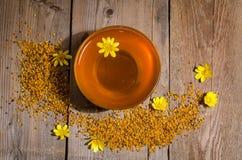 Miel en el bol de vidrio, el polen y las flores amarillas alrededor de él Imagenes de archivo