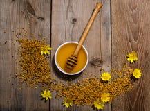 Miel en el bol de vidrio, el polen y las flores amarillas alrededor de él Foto de archivo