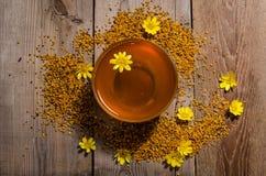 Miel en el bol de vidrio, el polen y las flores amarillas alrededor de él Foto de archivo libre de regalías