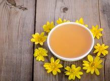 Miel en el bol de vidrio y las flores amarillas alrededor de él Imagen de archivo