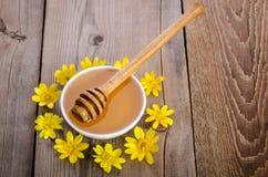 Miel en el bol de vidrio y las flores amarillas alrededor de él Imagenes de archivo