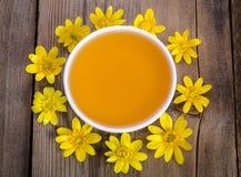 Miel en el bol de vidrio y las flores amarillas alrededor de él Foto de archivo libre de regalías