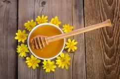 Miel en el bol de vidrio y las flores amarillas alrededor de él Fotografía de archivo