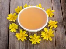 Miel en el bol de vidrio y las flores amarillas alrededor de él Foto de archivo
