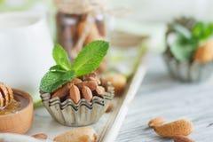 Miel en el cuenco, las hojas de menta, las almendras y el tarro de madera con leche en la bandeja de madera Fotografía de archivo libre de regalías