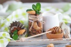 Miel en el cuenco, las hojas de menta, las almendras y el tarro de madera con leche en la bandeja de madera Imagenes de archivo