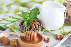 Miel en el cuenco, las hojas de menta, las almendras y el tarro de madera con leche en la bandeja de madera Fotos de archivo