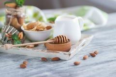 Miel en el cuenco, el muesli, las hojas de menta, las almendras y el tarro con leche en la bandeja de madera Fotos de archivo